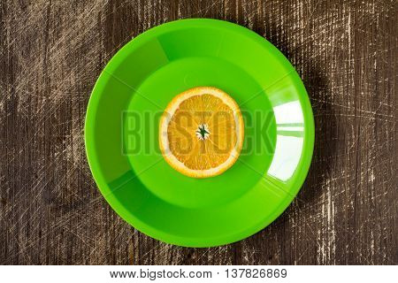 Orange slice in a green plate top view