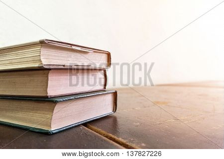Old books on a wooden table knowledge and learning concept soft focus vintage tone