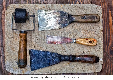 Retro design tools for artist workshop: rubber roller, different size putty knives on stone plate and wooden background. decorator tools accessories concept. up view
