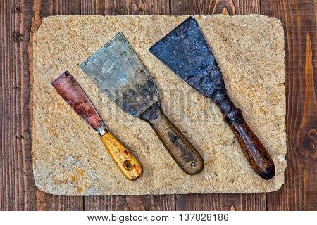 Rare putty spatula knives macro view. building decorator tools on stone plate and wooden table background. up view