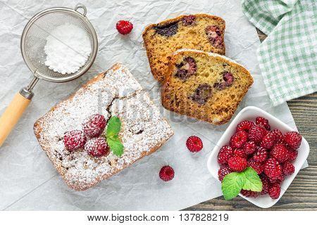 Sliced banana bread with raspberries cherries and white chocolate on parchment horizontal top view