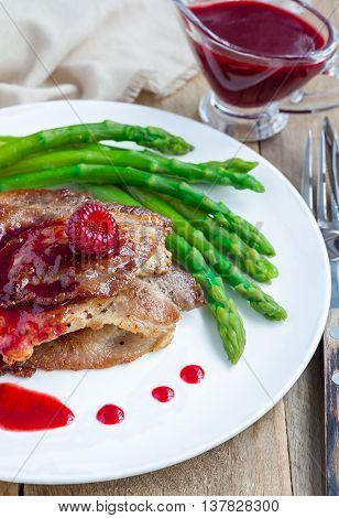 Pork cutlets with raspberry sauce and asparagus on white plate vertical