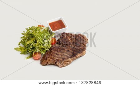 Grilled stake, green salad tomatoes and red spicy sauce. Barbecue meal concept. Gray background
