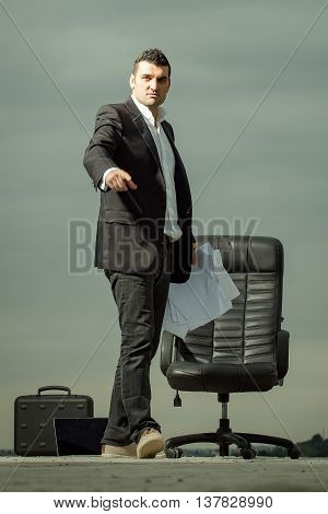 handsome tired male businessman in black formal jacket and white shirt with laptop and paper near leather arm chair outdoor with briefcase on cloudy sky background