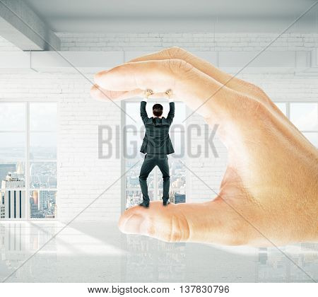 Businessman trapped between fingers of big hand on brick interior background. Pressure concept