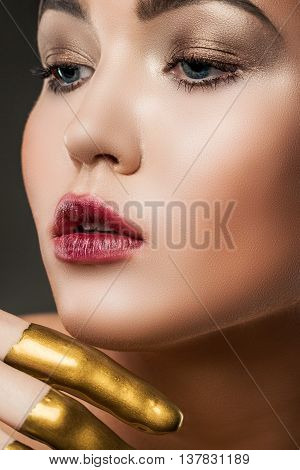 Close-up Portrait Of A Girl With Yellow Paint On His Face In The Studio On A Gray Background. Creati