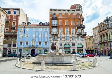 Trieste Italy June 1 2013: the circle fountain in the Ponterosso square with historic coloful buildings in the background.