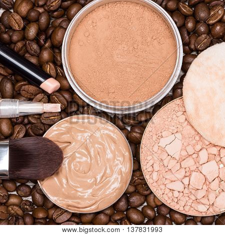 Close up of concealers, liquid foundation, loose and crushed compact powder on coffee beans. Basic makeup products to create the perfect skin tone and complexion