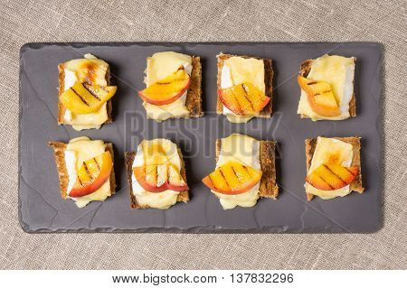 canapes appitizer with grilled brie and nectarine plated on a slate dish