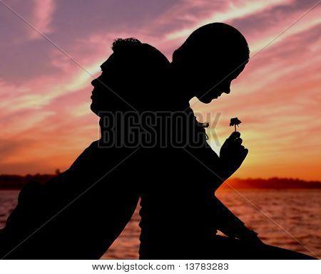 Silhouette der paar sitzen Rücken an Rücken auf Hintergrund von sunset