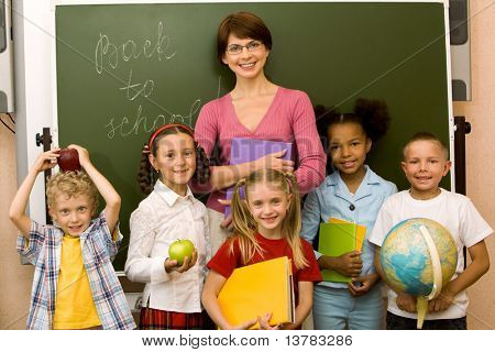 Group schoolchildren looking at camera with their teacher near by