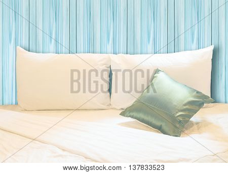 white pillow and green pillow on bed and with wrinkle messy blanket in vintage wooden bedroom from sleeping in a long night.