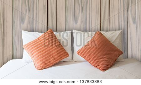 white pillow and orange pillow on bed and with blanket in vintage wooden bedroom