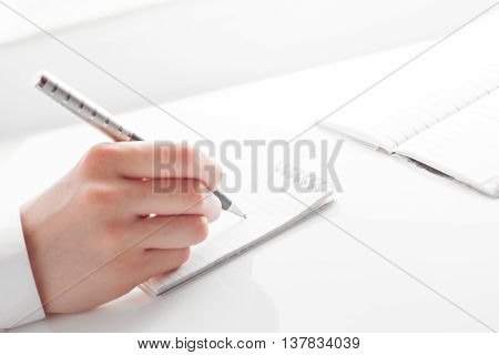 woman's hand writing entries in a notebook. studio shot