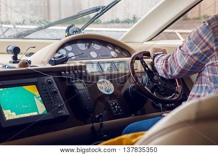 Saint Petersburg, Russia - 18 June : dashboard on small yachts that take tourists along the Neva river. at the helm sits a man 40 years old on international kissing day on 18 June, 2016.