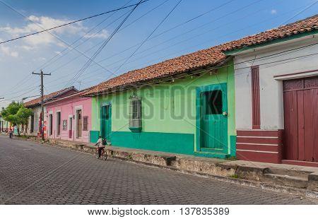 LEON, NICARAGUA - NOVEMBER 10, 2009: Street with colorful houses and a Nicaraguan cyclist