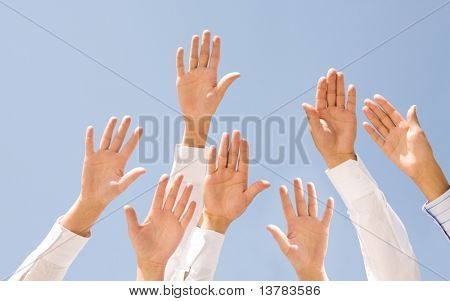 Image of several human palms raised against clear blue sky