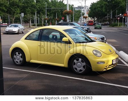 BRATISLAVA SLOVAKIA - CIRCA JUNE 2016: yellow Volkswagen Beetle parked in a car park in the city centre