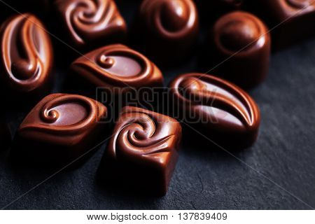 Delicious chocolate candies. Chocolates as background. Praline sweets. Low key photo
