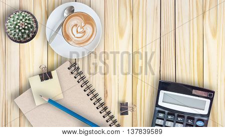cactus calculator vintage book clip blue pencil and latte coffee cup on vintage wooden table
