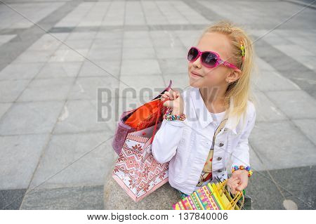 Fashionably dressed little girl with shopping bags. Young little girl with full shopping bags standing near boutique. Blond girl in sunglasses. Point of shooting from above.