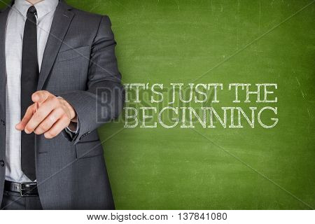 Its just the beginning on blackboard with businessman finger pointing