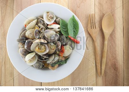 Puff meretrix or Meretrix casta is Seashell in white dish on wooden background This menu seafoods of Local Thai foods.