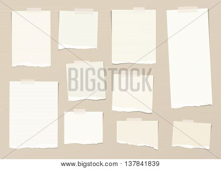 Pieces of light brown torn note paper with adhesive, sticky tape are stuck on background.