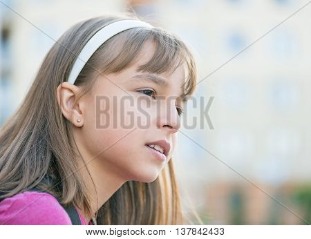 Outdoor portrait of little cute girl 10-11 year old with hoop on head