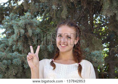 Girl of Slavic appearance against a fir-tree