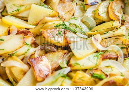 Delicious fried potatoes with onion and fresh dill closeup. Selective focus very shallow depth of field