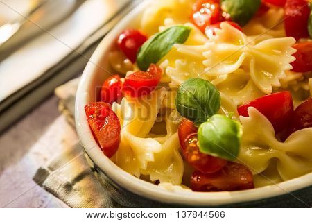 Closeup of Italian Farfalle pasta with tomatoes and basil over a colored background