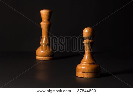 chess pieces made out of wood on a black background