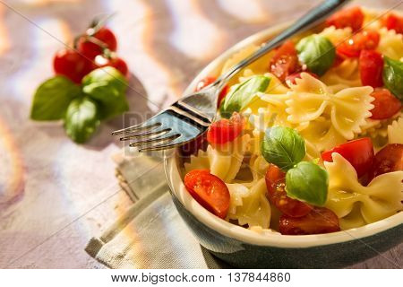 Closeup of Italian Farfalle pasta with tomatoes basil and fork over a colored background