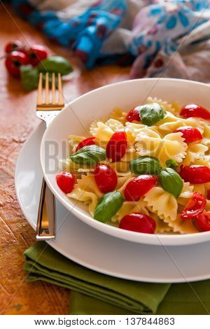 Farfalle pasta with cherry tomatoes and basil over a green napkin