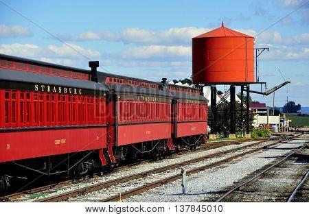 Strasburg Pennsylvania - October 16 2015: Three vintage wooden passenger cars and steam engine water tower at the Strasburg Railroad