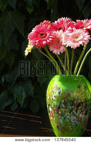 Colorful gerbera daisies in green vase made from mosaic murano glass
