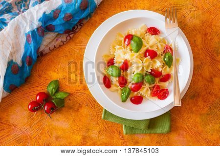 Farfalle pasta with cherry tomatoes and basil seen from above over a colored background