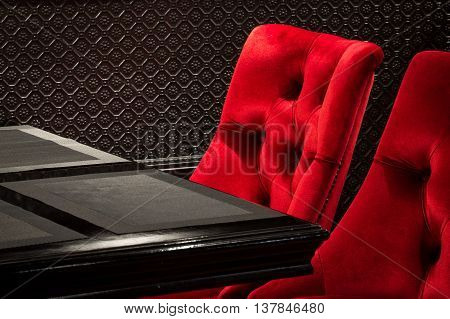 Red velvet chairs and table black, elegant piece of interior of restaurant