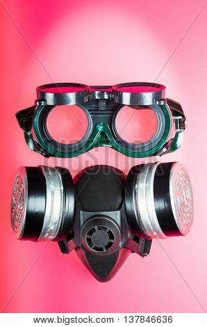 goggles and a mask with filters for toxic fumes and chemicals to form a disturbing form of a face on a red background