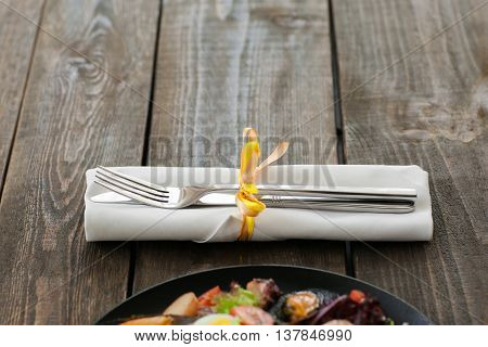 Cutlery on brown wooden background with seafood, void. Horizontal position of white napkin with knife and fork, seafood meal in downside of image, copyspace on wood. Focus on restaurant cutlery