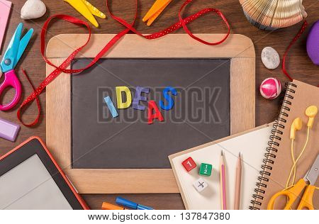Ideas word formed by color wooden alphabets on small blackboard with school supplies on wooden table
