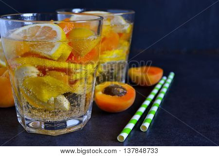 Cold Summer lemonade with peach and apricot on the black background