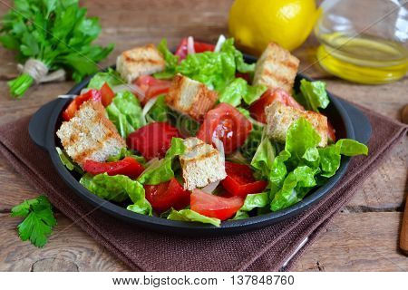 Vegetable salad with romano tomatoes peas and croutons on a concrete background