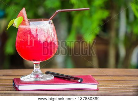 Water melon smoothie on wooden table with notebook and pen