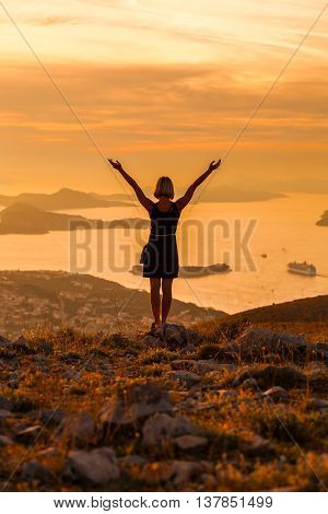 Female tourist standing on the background of Bay at sunset. Misty layers of islands. Sunset in Adriatic sea with layers mountains on the horizon. Hills, growing out of the water. Dubrovnik. Croatia.