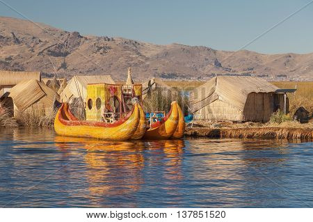 Reed boat on Island of Uros. Those are floating islands on lake Titicaca located between Peru and Bolivia. Colorful image with yellow boat and clear blue sky.