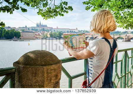 Pretty young female tourist studying a map against the background of the old town and the Vltava River in Prague. Czech Republic. Lost in the city. Travel Czech Republic.