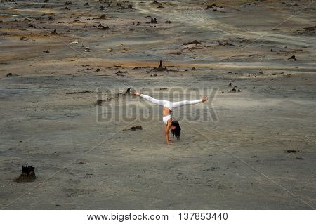 flexible gymnast girl in a beautiful pose on a background of apocalyptic landscape in the desert, Russia, the city of Karabash
