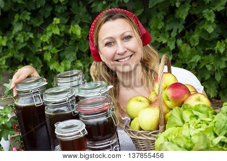 A market woman with many jars of honey and a basket of apples